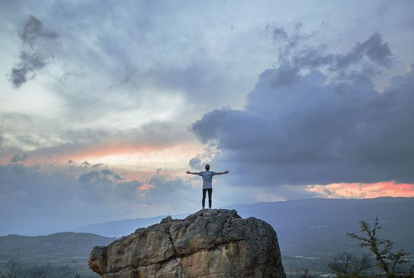 person standing on cliff with arms spread
